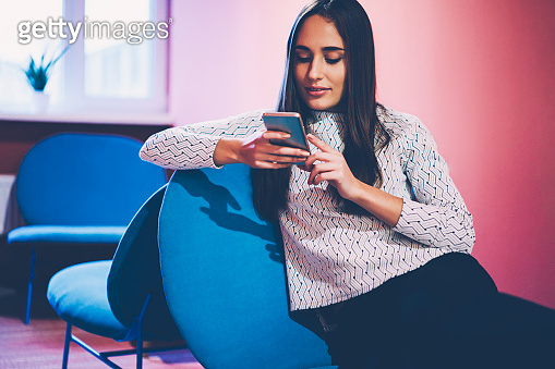 Positive brunette hipster girl reading news from social networks via smartphone resting in cafe interior,young female blogger share photo and video with followers texting message on telephone
