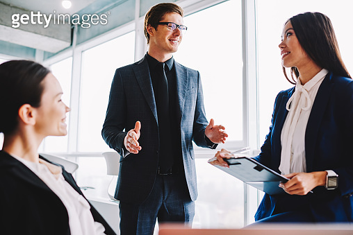 Cheerful male boss enjoying business meeting with female employees talking about corporate, successful professional experts smiling and communicating about finance and trade in company office