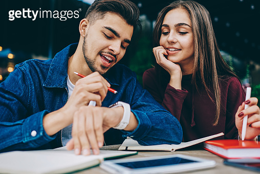Cheerful hipster guy showing his girlfriend useful application on wearable pc spending time together,man checking notification on smartwatch satisfied with modern gadget and apps talking with colleague