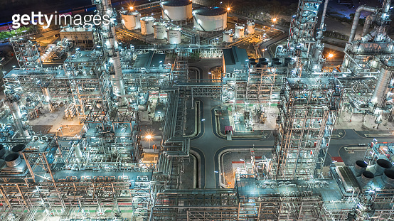 Oil refinery plant form industry zone, Aerial view oil and gas industrial, Refinery factory oil storage tank and pipeline steel at night.
