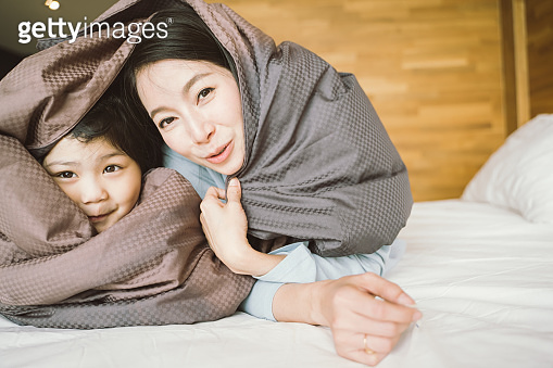 Mother and her daughter child girl playing in the bedroom and putting blanket on . Happy Asian family