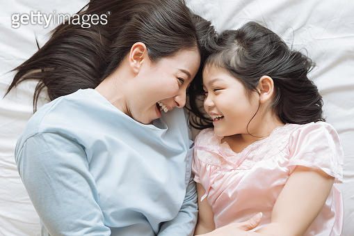 Mother and her daughter child girl playing in the bedroom .Happy Asian family
