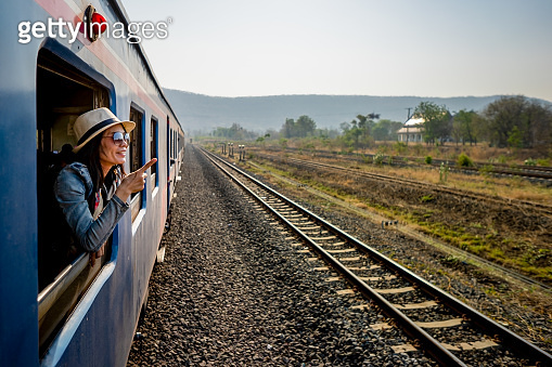 Happy woman tourist exciting for journey by train, she smiling and looking view on window of train