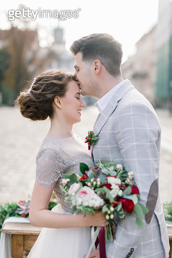 Happy groom kisses his gorgeous bride. Old city buildings and wedding decor on the background