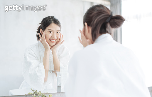 Female Skin Care. Young asian woman touching her face and looking to mirror in bathroom