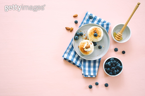 Cottage cheese pancakes or syrniki with sour cream and blueberry