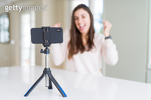 Beautiful young woman recording selfie video with smartphone webcam screaming proud and celebrating victory and success very excited, cheering emotion