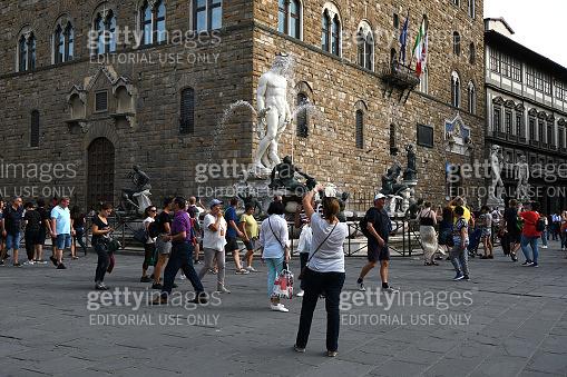 Tourists and the Neptune fountain in Signoria square (Piazza della Signoria) with the town hall on the background. Italy.