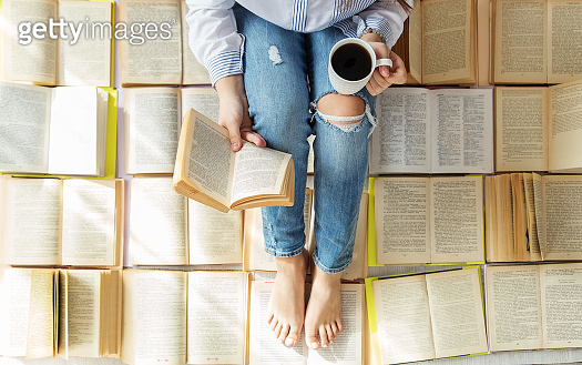 A young woman reads a book and drinks coffee. A lot of books. Concept for World Book Day, lifestyle, study, education.