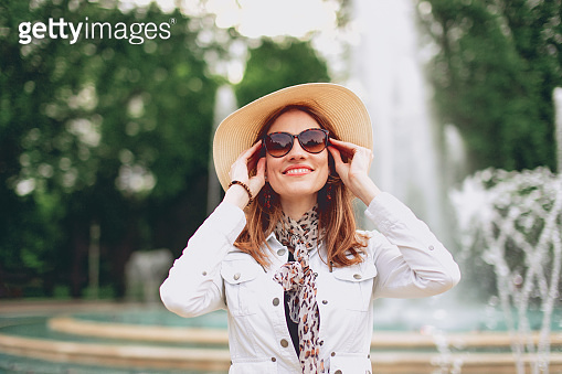 Happy young woman in hat at park with fountain holding sunglasses portrait