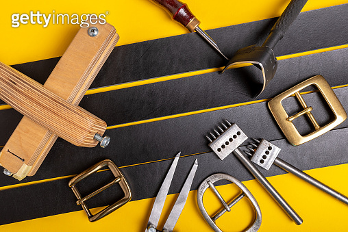 Sewing process of the leather belt. Tools, materials and accessories for leather workshop. Vintage sewing industrial