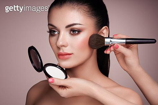 Beautiful woman applies skin tone with brush