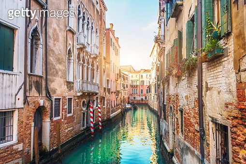 Narrow streets with canals and apartment buildings in Venice, Italy.