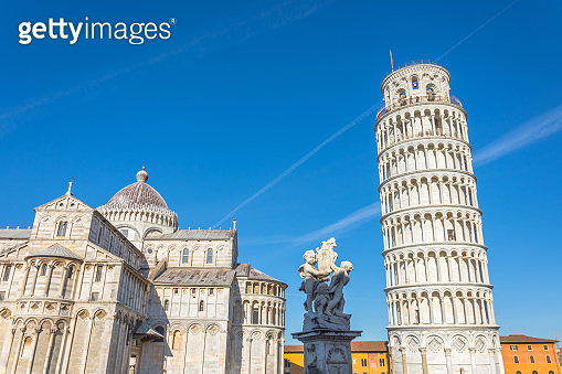 Pisa cathedral and the leaning tower and sculpture in a sunny day in Pisa, Italy.