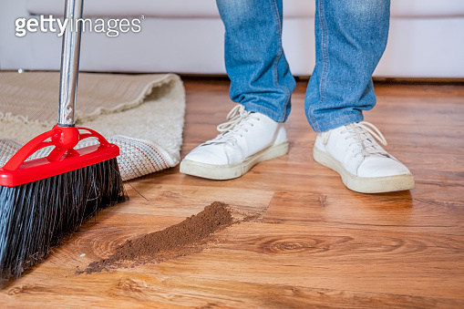 Housekeeping concept close up of broom sweeping floor at home