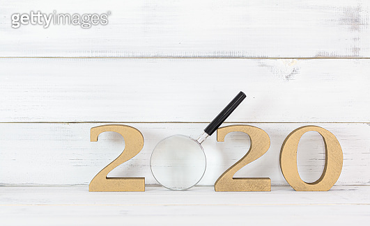 Upcoming 2020 New Year with Magnifying glass over white wood background, Search Goals Conccept.