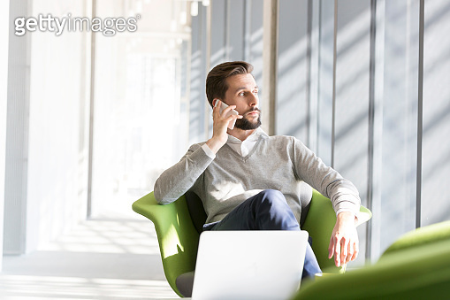 Businessman talking on mobile phone while sitting on chair at office
