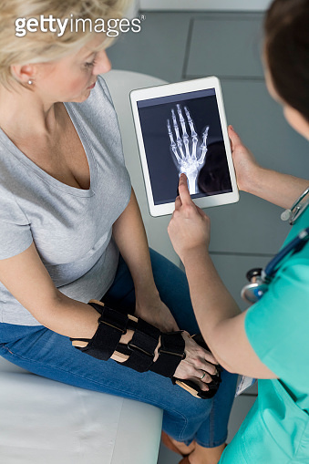 Nurse showing x-ray on digital tablet to mature patient at hospital