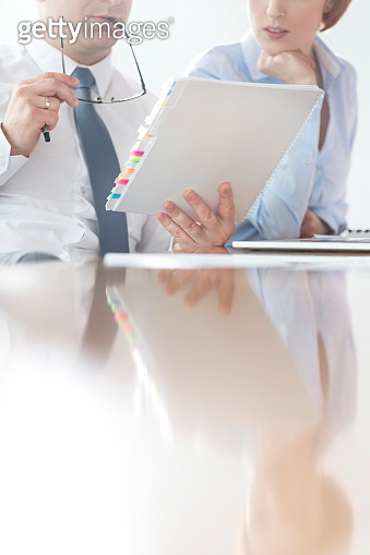 Midsection of businessman and businesswoman discussing over document in boardroom at office