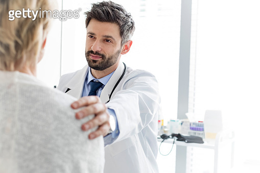 Mid adult doctor consoling mature patient at hospital