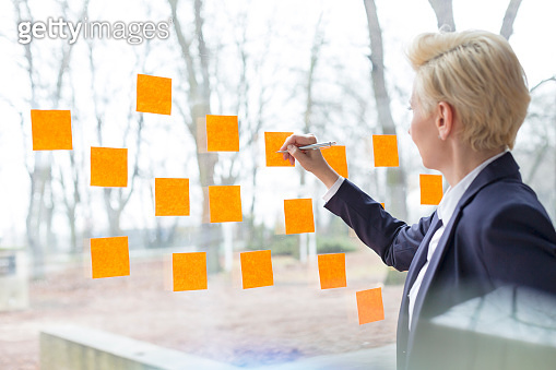 Confident mature businesswoman writing on orange adhesive notes stuck on glass window at office