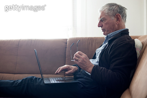 Senior Man Using Laptop on Sofa in Living Room