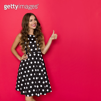 Smiling Beautiful Young Woman In Black Coctail Dress In Polka Dots Is Looking Away And Showing Thumb Up
