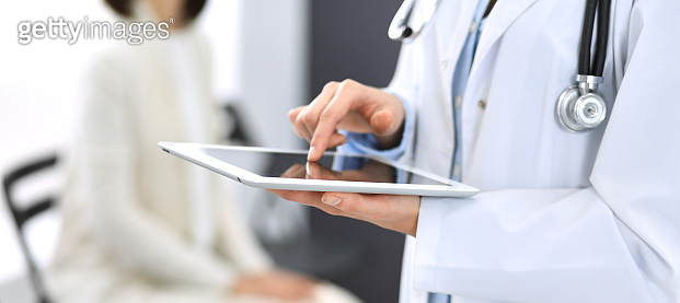 Female physician using digital tablet  while standing near reception desk at clinic or emergency hospital. Unknown doctor woman at work. Medicine concept