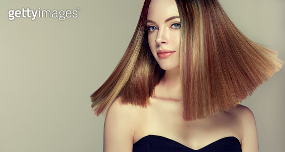 Young, brown haired beautiful model with middle length, straight, well groomed hair. Hair care and hairdressing art.