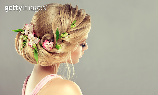 Fresh flowers inserted in elegant hairstyle of pretty, young model. Hairdressing art and beauty maintenance.
