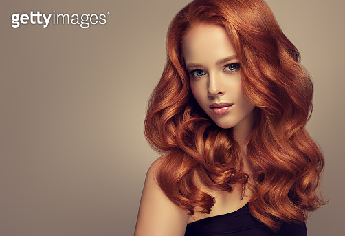 Young, red haired beautiful model with long,  curly, well groomed hair. Excellent hair waves. Hairdressing art and hair care.