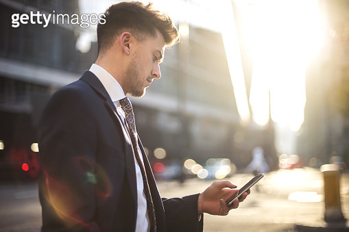 Handsome businessman checking his phone while walking in the street