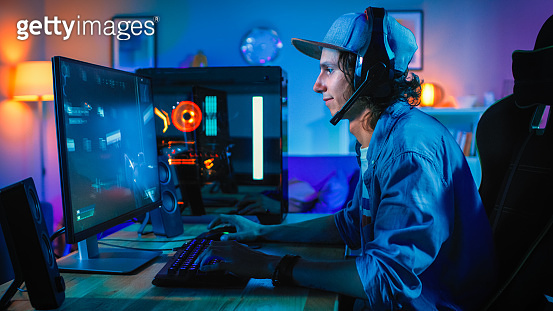 Professional Gamer Playing First-Person Shooter Online Video Game on His Powerful Personal Computer. Room and PC have Colorful Neon Led Lights. Young Man is Wearing a Cap. Cozy Evening at Home.