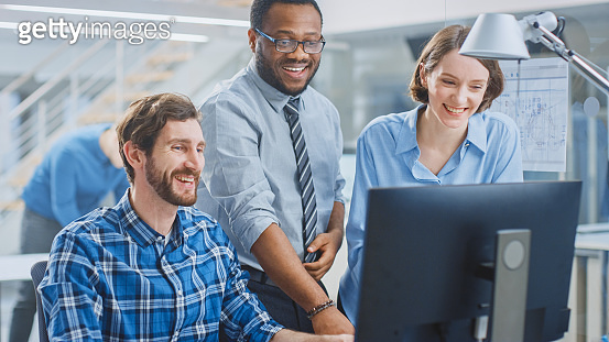 In the Industrial Engineering Facility: Male Engineer Working on Desktop Computer, Female Chief Engineer and Project Manager Finish with the Project. They Smile, Joke and Celebrate Success and Smile