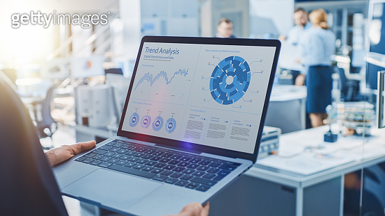 Stylish Female Industrial Robotics Engineer Uses Laptop Computer with Graphs and Diagrams in Trend Analytics Software. Technology Research Facility for Machine Learning and Cloud Computing