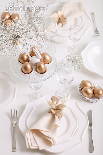 Happy Easter! Golden decor and table setting of the Easter table with white dishes of white color.