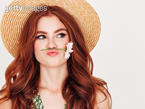 Beautiful woman with red hair holding a flower