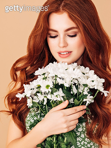 Beautiful woman with red hair holding bouquet
