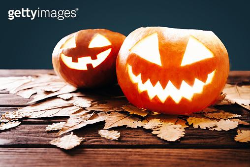 Two Halloween glowing jack-o-lantern pumpkins.