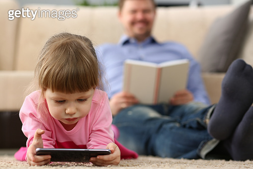 Father and daughter lie on floor using mobile phone