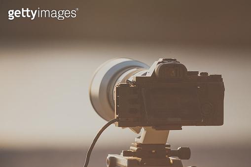 Camera DSLR set on tripod capturing sunset on beach.