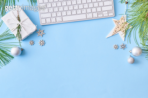 Flat lay christmas home office desk with pine branches and keyboard, christmas decorations on a blue background