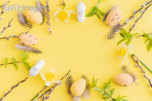 Flat lay easter composition with yellow daffodils and eggs on a yellow background