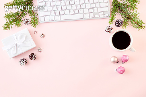 Flat lay christmas home office desk with spruce branches and keyboard, christmas decorations on a colored background