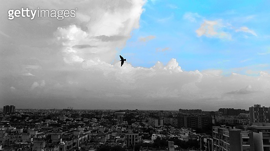 Dramatic Blue sky with full of monsoon clouds and cityscape of ahmedabad buildings birds on horizon of new india.