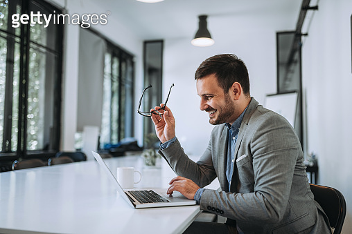 Man laughing in office while looking at laptop.