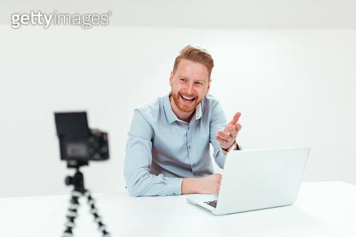 Positive millenian man talking toward camera for his vlog.