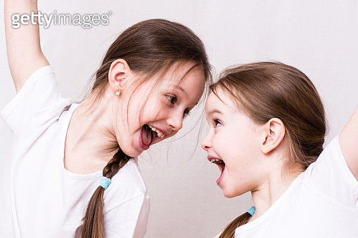 Two girls sisters emotionally smile at each other