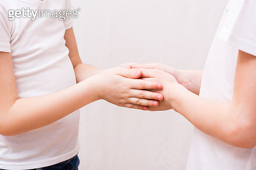 Two children carefully hold each other's palms