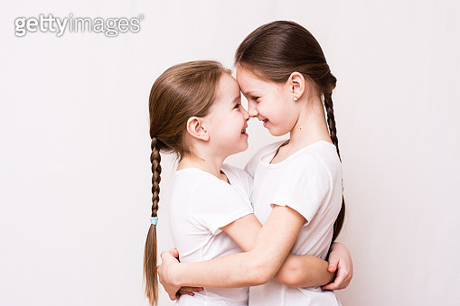 Two girls sisters gently hug each other when meeting
